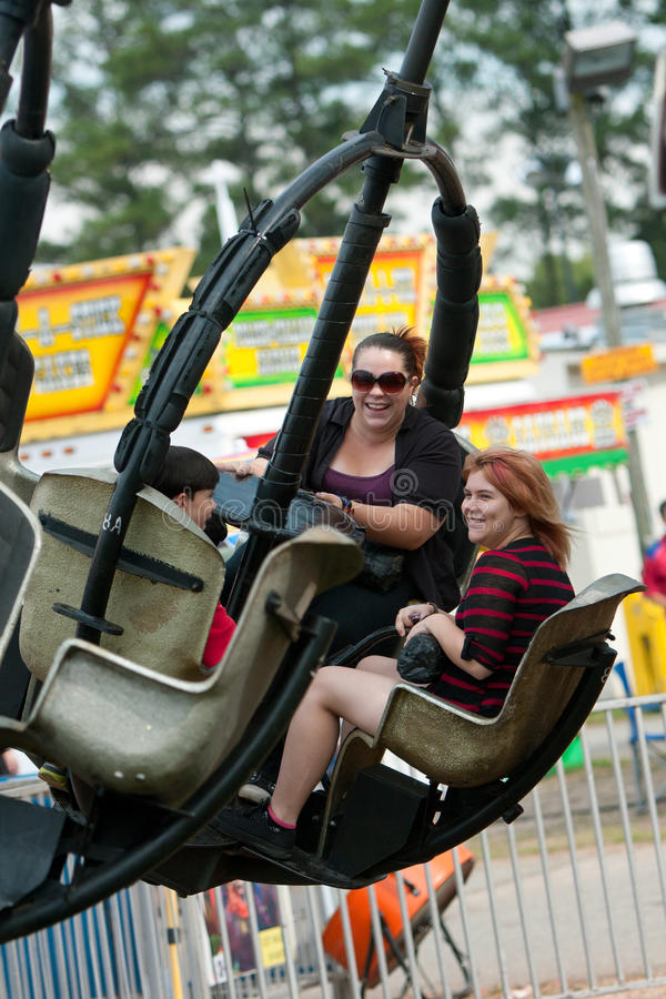 Family Enjoys Carnival Ride At County Fair royalty free stock image