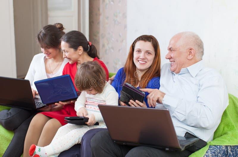 Family enjoys on sofa with few laptops stock photos
