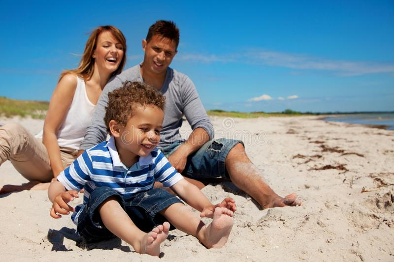 Family Enjoys Vacation on a Beach. Young family enjoys their vacation on a bright sunny beach royalty free stock photos