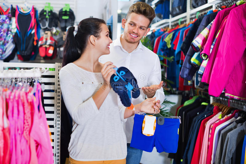 Family examining various swimsuits for children in sports store. Smiling happy positive family examining various swimsuits for children in sports store royalty free stock photos