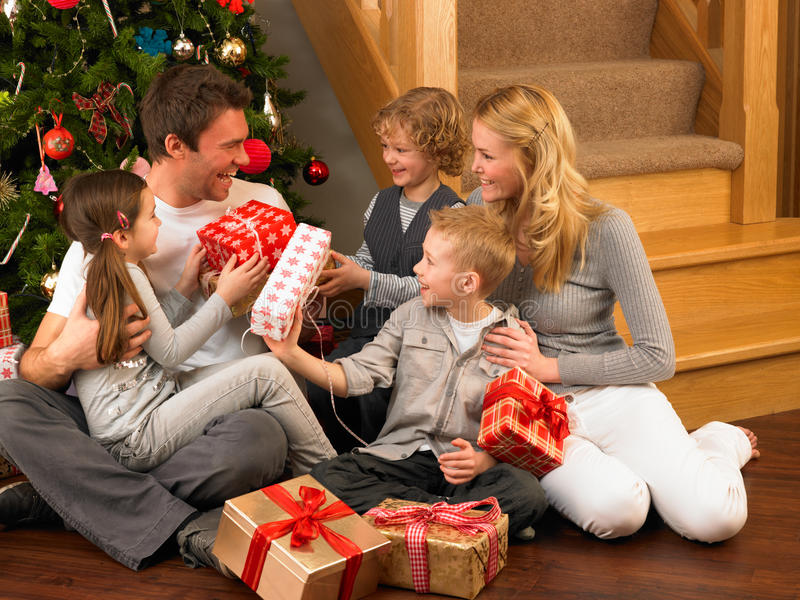 Download Family Exchanging Gifts In Front Of Christmas Tree Stock Photo - Image: 20461798