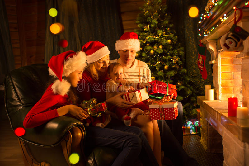 Family exchanging gifts in front of fireplace at Christmas tree. Family exchanging gifts sitting in front of fireplace at Christmas tree royalty free stock images