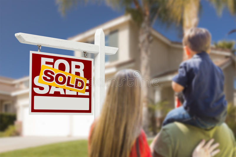 Family Facing Sold For Sale Real Estate Sign and House. Curious Family Facing Sold For Sale Real Estate Sign and Beautiful New House stock photos