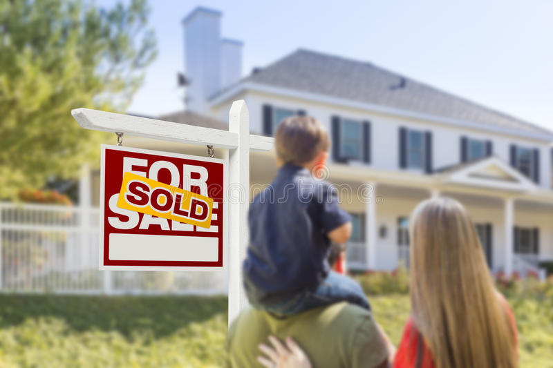 Family Facing Sold For Sale Real Estate Sign and House. Curious Family Facing Sold For Sale Real Estate Sign and Beautiful New House stock photo