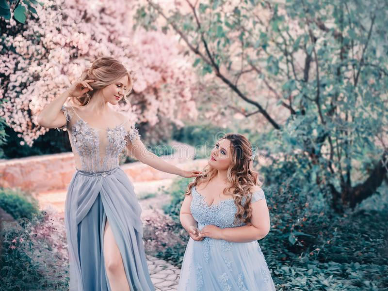 Family fairy photo shoot. Two blond women with wavy hair in luxurious, fabulous, blue dresses against the backdrop of. Flowering gardens. Artistic Photography royalty free stock image