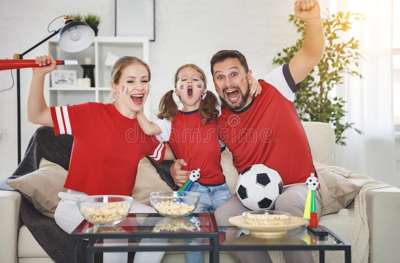 Family of fans watching a football match on TV at home royalty free stock photos