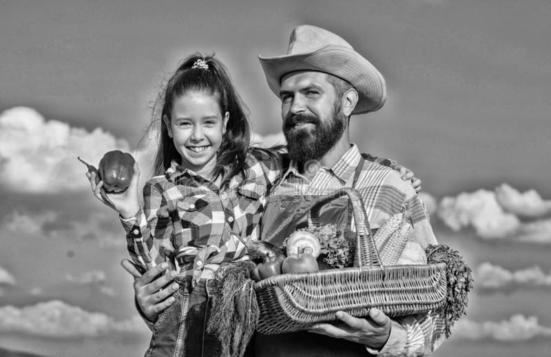 Family farm concept. Only organic and fresh harvest. Man bearded rustic farmer with kid. Farmer family homegrown harvest stock photography