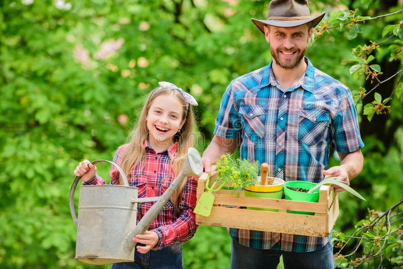 Family farm. spring village country. ecology. Watering can and shovel. little girl and happy man dad. earth day. father. And daughter on ranch. Beautiful royalty free stock photo