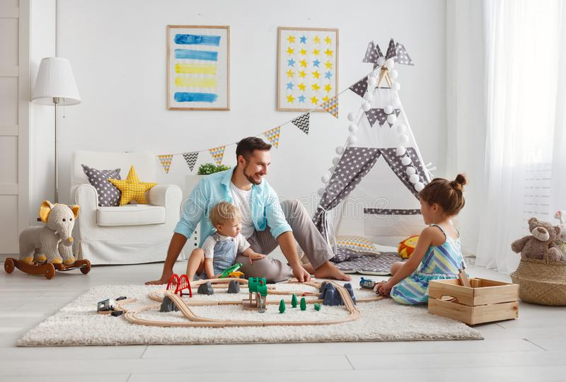 Family father and children play a toy railway in playroom. Family father and children play a toy railway in the playroom stock photos