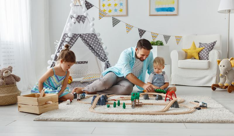 Family father and children play a toy railway in playroom. Family father and children play a toy railway in the playroom royalty free stock photo