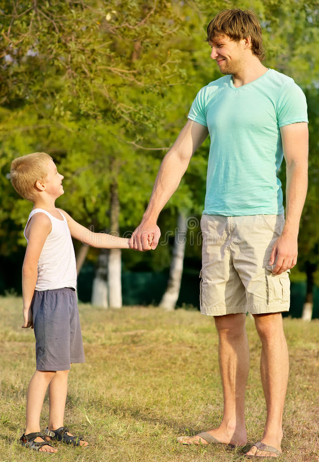 Family Father Man and Son Boy Child holding hand in hand Outdoor stock photo