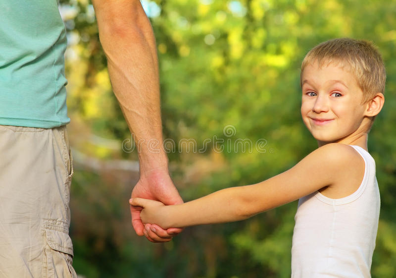 Family Father Man and Son Boy Child holding hand in hand Outdoor stock photography