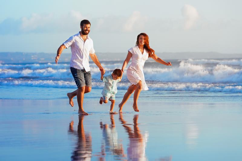 Family - father, mother, baby run on sunset beach. Happy family - father, mother, baby son have fun together, child run with splashes by water pool along sunset royalty free stock images