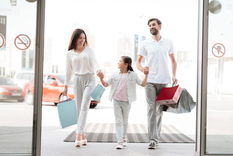 Family, father, mother and daughter are entering shopping mall. royalty free stock image