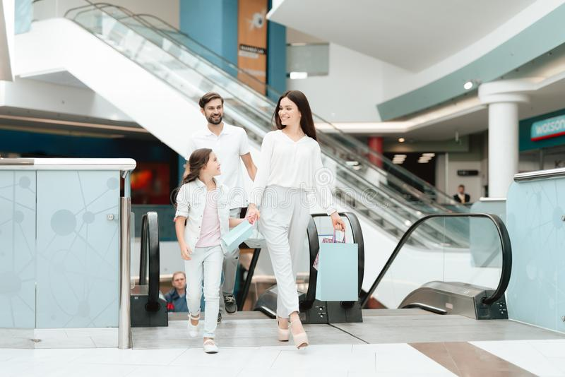Family, father, mother and daughter are going up on escalator in shopping mall. royalty free stock images
