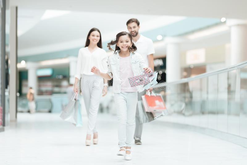 Family, father, mother and daughter are walking to another store in shopping mall. Girl is running. stock photo