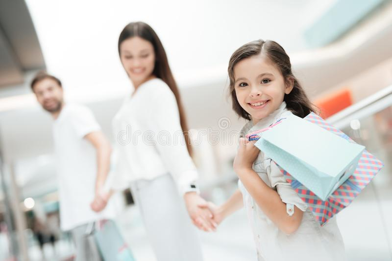 Family, father, mother and daughter are walking from one store to another in shopping mall. stock image