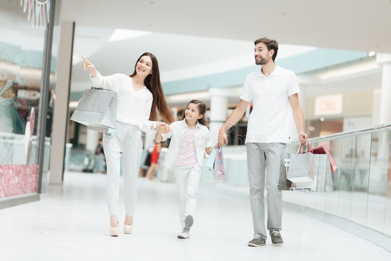 Family, father, mother and daughter are walking to another store in shopping mall. stock photography