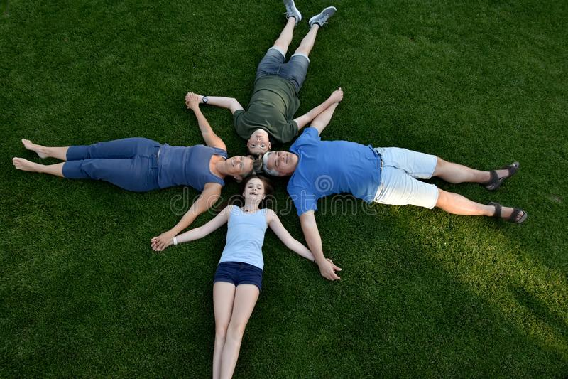 Family, father, mother, son and daughter lying in the meadow royalty free stock image