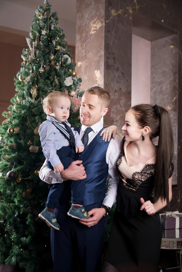 Family, father mother and son near Christmas tree. Eve royalty free stock image