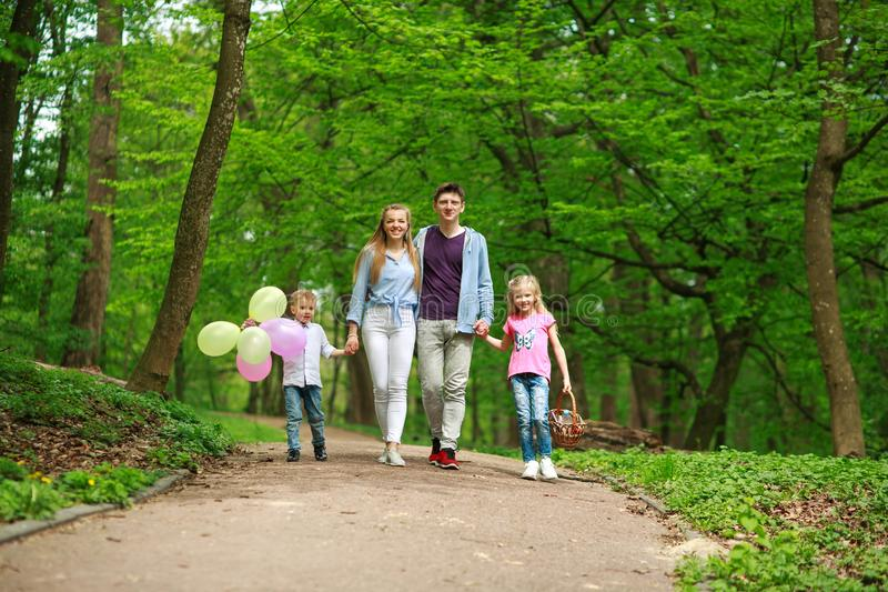 Family father and mother with two kids walking in summer green city park on picnic, happy holidays parents and children on nature royalty free stock image