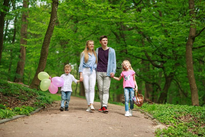 Family father and mother with two kids walking in summer green city park on picnic, happy holidays parents and children on nature royalty free stock photography