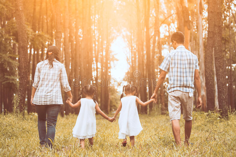 Family father, mother and two little child girls holding hand. And walking together in the park at sunset stock photos