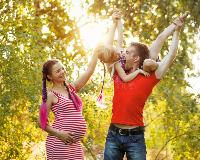 Family. Father, pregnant mother and daughter outdoors. Walk in the city park. Parents fool around with the child. The father lifted the child on his shoulders royalty free stock photography