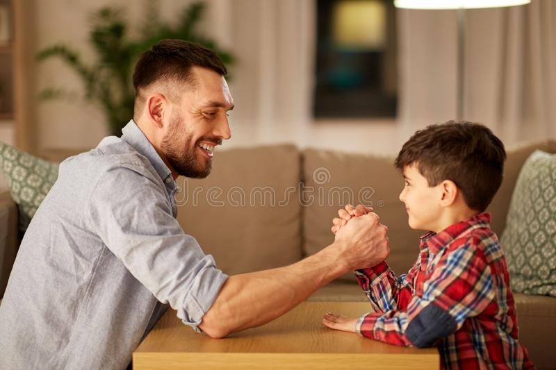 Happy father and little son arm wrestling at home. Family, fatherhood and people concept - happy smiling father and little son arm wrestling at home in evening stock images