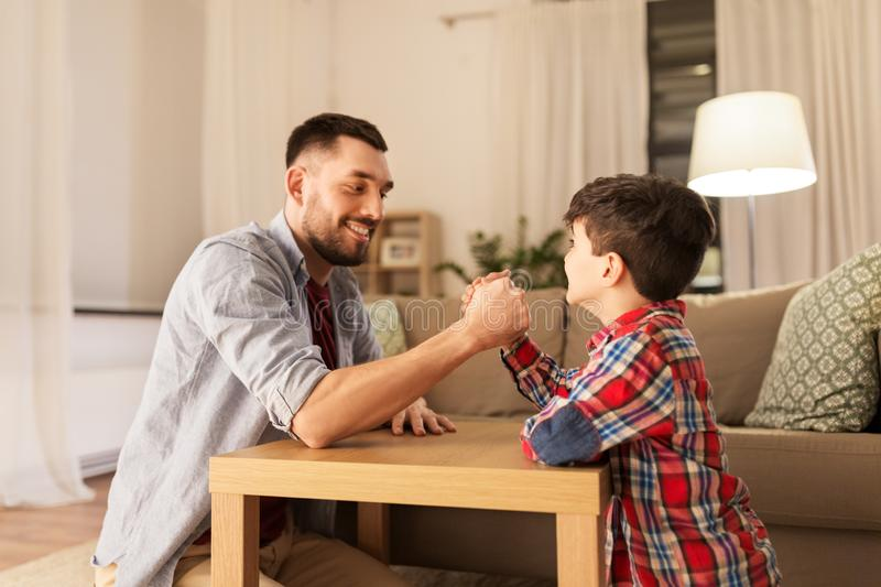 Happy father and little son arm wrestling at home. Family, fatherhood and people concept - happy smiling father and little son arm wrestling at home in evening royalty free stock photo