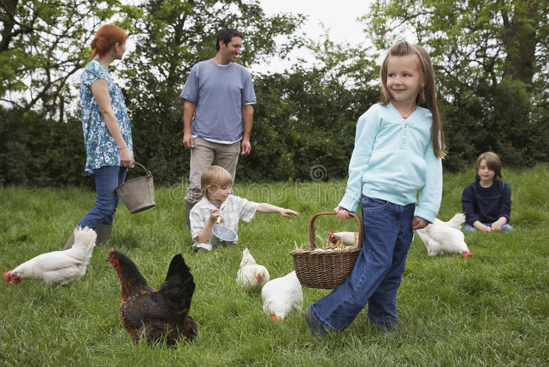 Family Feeding Hens On Grassland stock photos