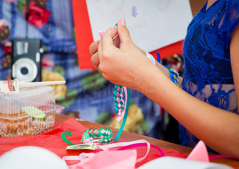 Family festival in Zaporozhye, Ukraine. ZAPOROZHYE, UKRAINE - SEPTEMBER 5, 2015. Bracelets braiding workshop during family festival organized by Charity Fund stock photos