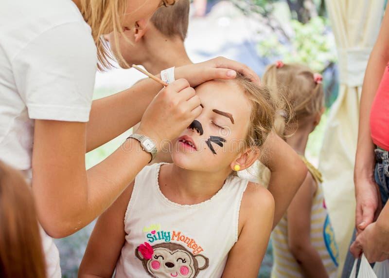 Family festival in Zaporozhye, Ukraine. ZAPOROZHYE, UKRAINE - SEPTEMBER 5, 2015. Volunteer painting cat mask on girl face during family festival organized by royalty free stock images