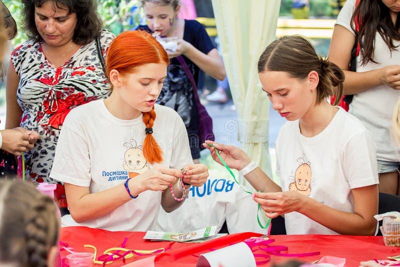 Family festival in Zaporozhye, Ukraine. ZAPOROZHYE, UKRAINE - SEPTEMBER 5, 2015. Volunteers at bracelets braiding workshop during family festival organized by stock image