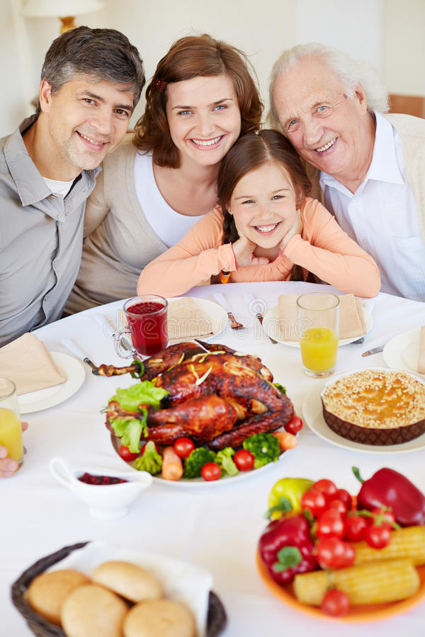 Family by festive table. Portrait of parents, their daughter and senior men sitting at festive table and looking at camera stock photography
