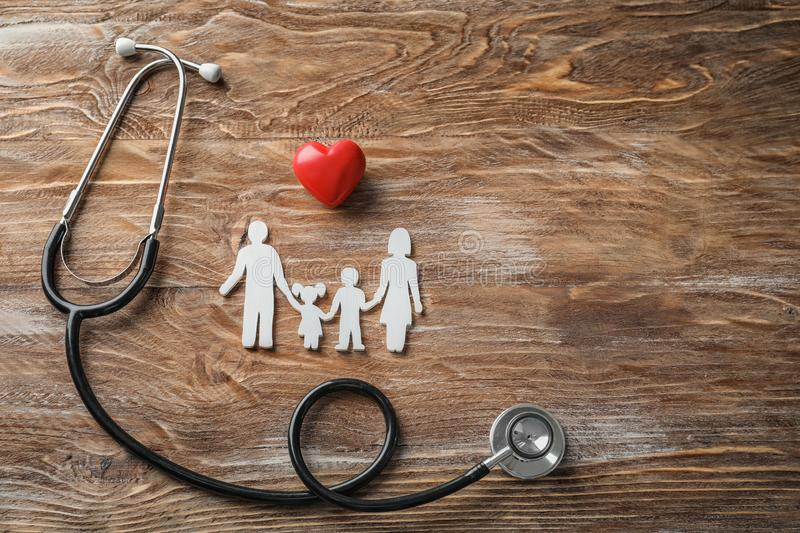 Family figure, red heart and stethoscope on wooden background. Health care concept royalty free stock photo