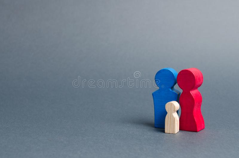 Family figures are standing on a gray background. Parents and child. Family values. Cell society, procreation. Programs to support. Young people, affordable royalty free stock photo