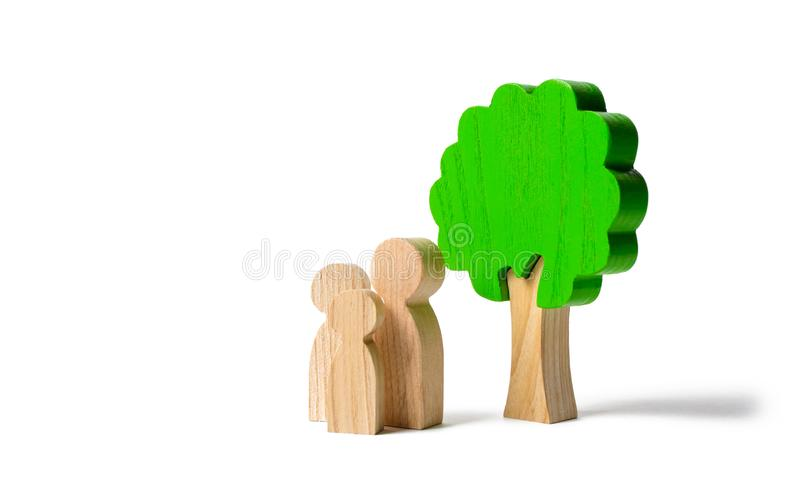 Family figures are standing near the tree on an isolated background. Pastime with family, kinship and parenting. Instilling good. Qualities and values in a royalty free stock images
