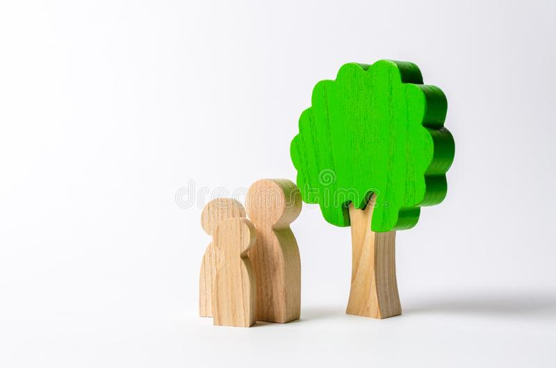 Family figures are standing near the tree. Pastime with family, kinship and parenting. Instilling good qualities and values in a. Healthy society. The concept royalty free stock image