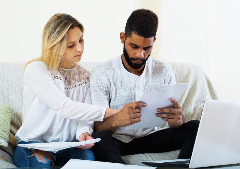 Family filling papers for mortgage. Interracial serious family filling papers for mortgage indoors stock photos