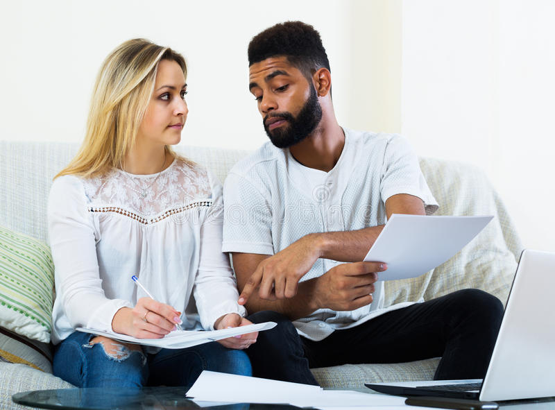 Family filling papers for mortgage. Interracial serious young family filling papers for mortgage indoors stock photo