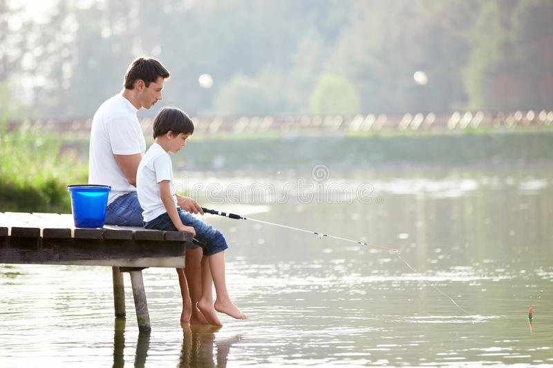 Family fishing. Man and boy fishing on the lake royalty free stock photography