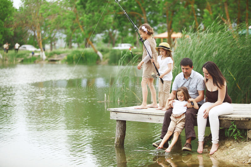 Family fishing. Young happy family with kids fishing in pond in summer