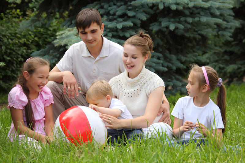 Family of five sit on grass with ball stock photography