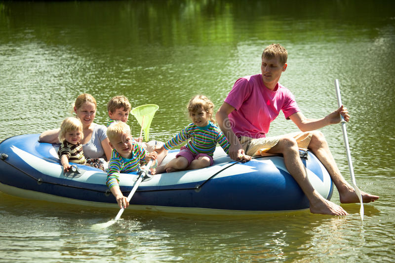Family float on an inflatable boat and fish net. Children and adults float on an inflatable boat and fish a net royalty free stock photo