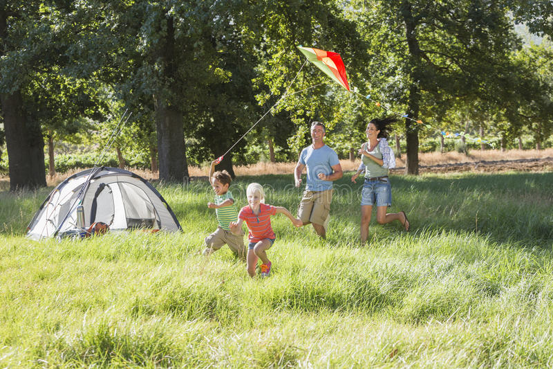 Family Flying Kite On Camping Holiday In Countryside stock photography