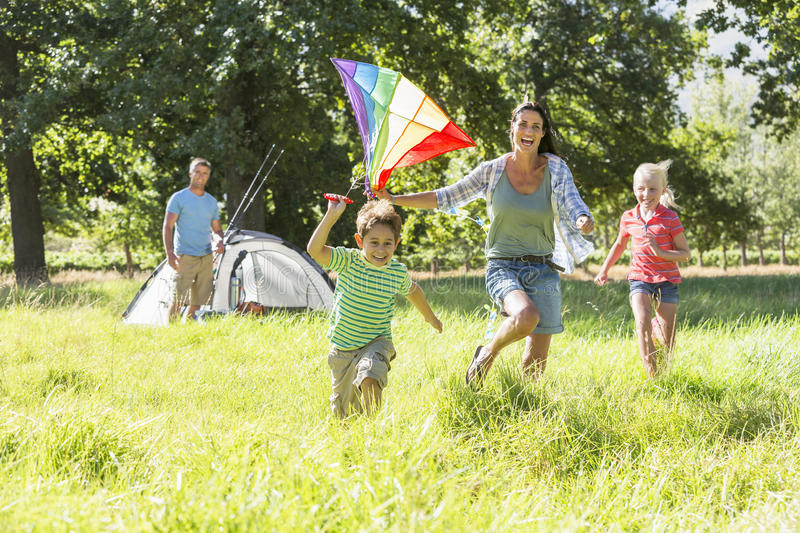 Family Flying Kite Camping Holiday In Countryside royalty free stock image