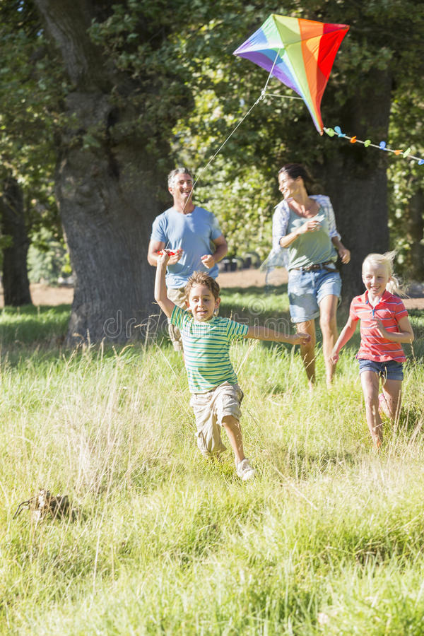 Family Flying Kite On Holiday In Countryside royalty free stock photos