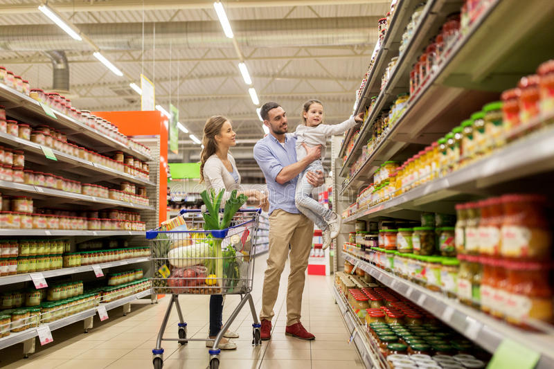Family with food in shopping cart at grocery store stock photo