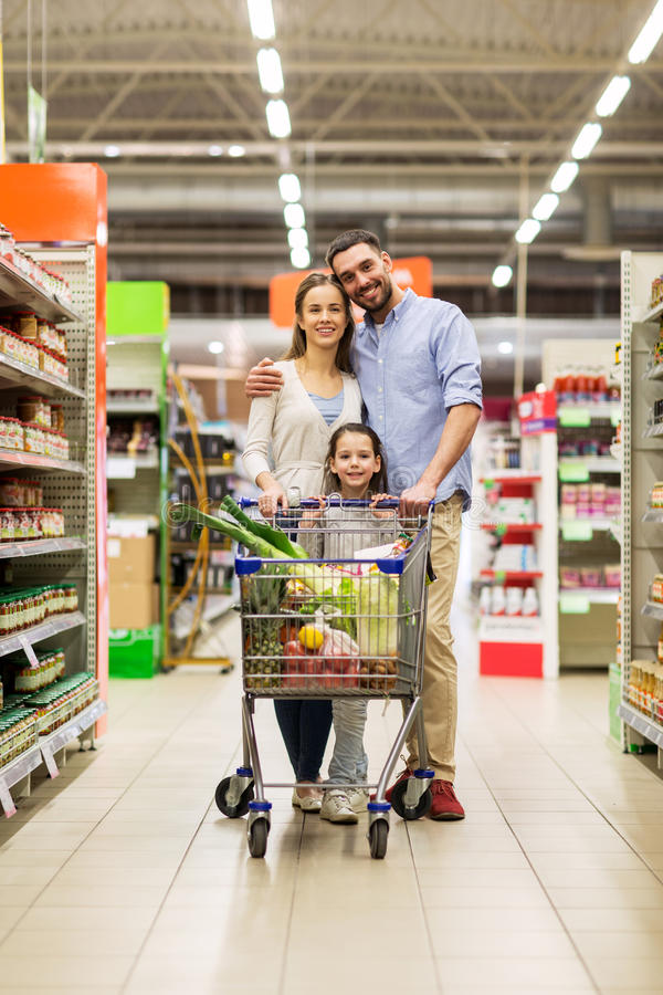 Family with food in shopping cart at grocery store stock photography